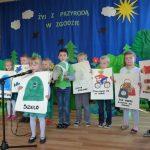 """Dzieci prezentują prace plastyczne na temat """"Żyj z przyrodą w zgodzie""""."""